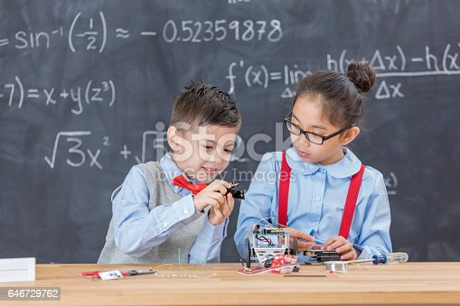 1016655140 istock photo Smart kids work on building robots together 646729762