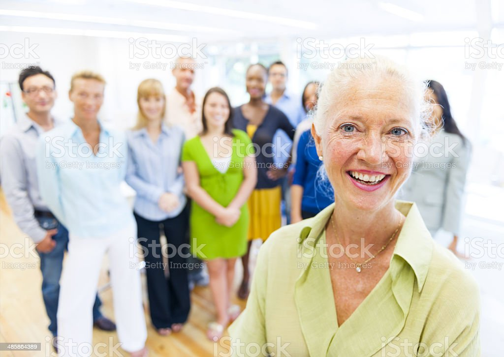 Smart Lady with colleagues in the background stock photo