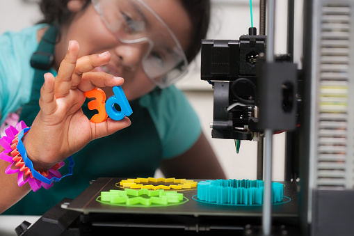 istock A smart latino student wearing multi-colored 3d printed shapes as jewelry, next to a 3d printer with designs on the heated print bed, and holding 3d letters in her hand. 1211433580