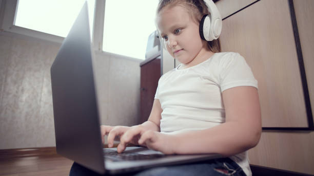 A smart little girl of seven years old in white headphones with a laptop in her hands is pushing on the floor in her room. The young generation on the Internet and IT technology stock photo