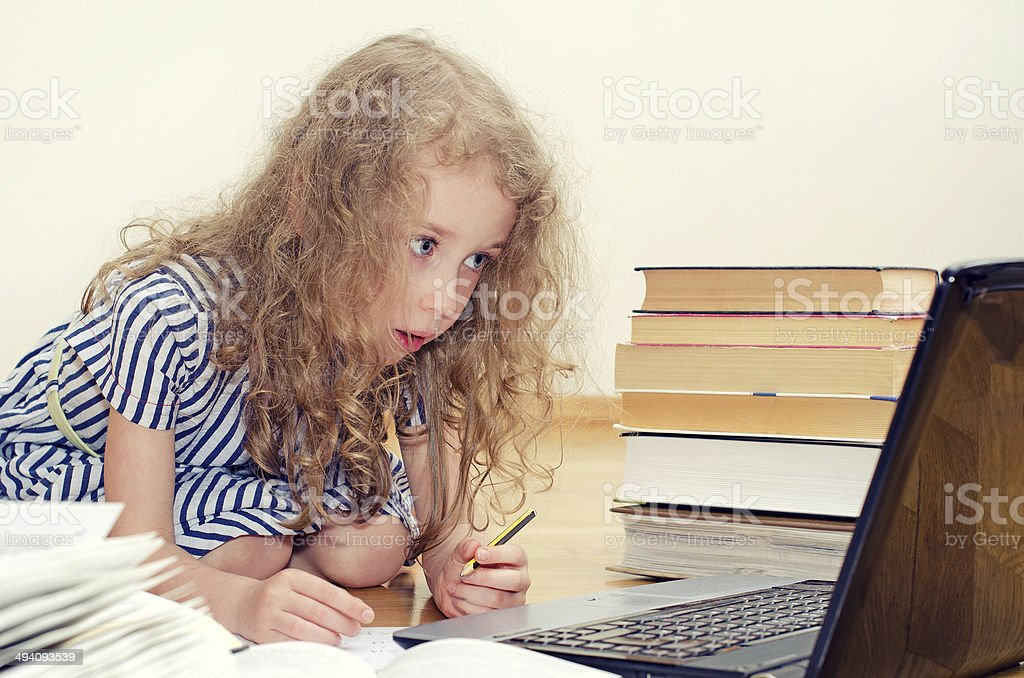 Smart little girl writes diploma at home. stock photo