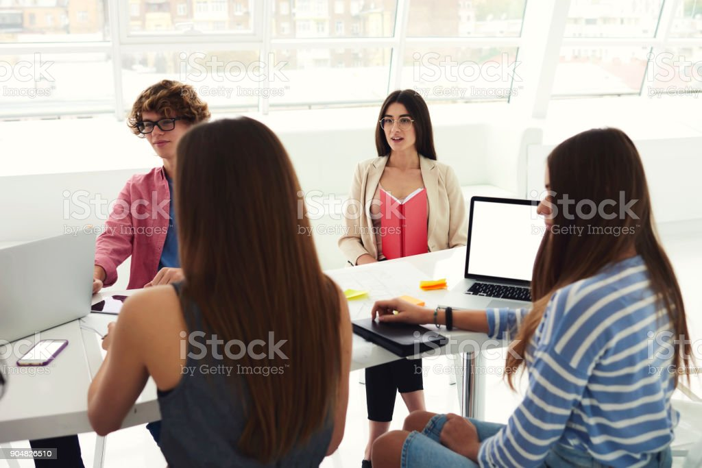 Smart male and female students in eyeglasses communicating with each other and collaborating on training project during corporate brainstorming sitting at conference table with laptop computer stock photo
