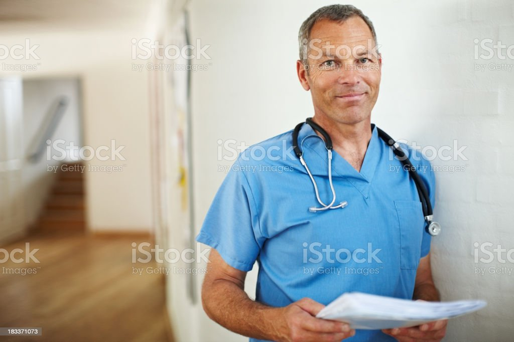 Smart male doctor in uniform at a hospital corridor stock photo