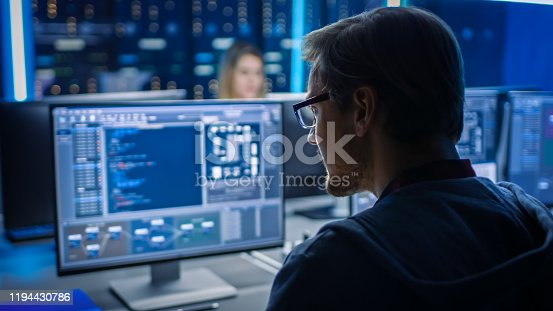 Smart Male IT Programer Working on Desktop Computer in Data Center Technical System Control Room. Team of Young Professionals Programming in Coding Language