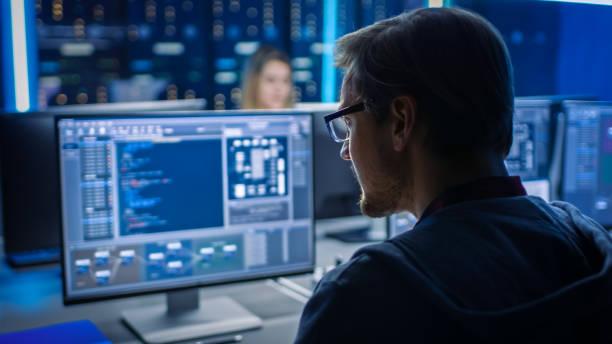 Smart Male IT-Programmierer arbeiten auf Desktop-Computer in Data Center Technical System Control Room. Team von Young Professionals Programmierung in Codierungssprache – Foto