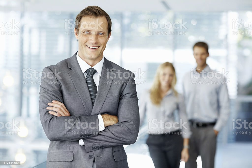 Smart male leader standing in front of his team royalty-free stock photo