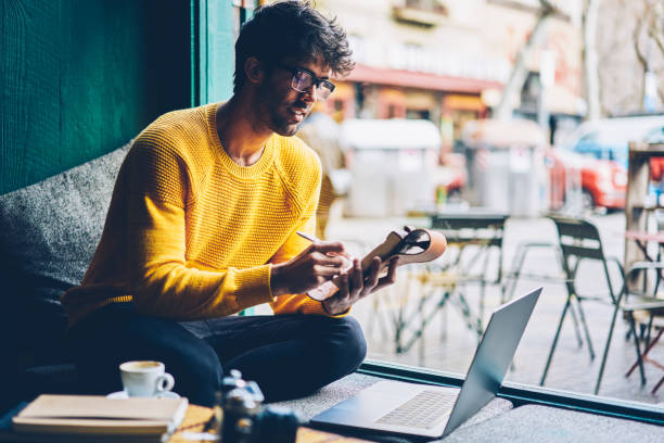 Smart male student in optical eyeglasses watching online webinar and making notes in notepad during e-learning in coworking space.Clever young man writing text in notebook from internet website stock photo