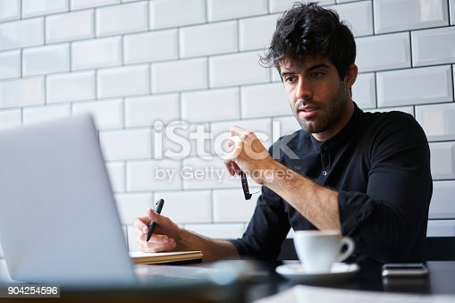 904263506 istock photo Smart male student watching webinar about developing business ideas on modern laptop and noting important information in notebook for future using sitting in coworking space with free 4G internet 904254596