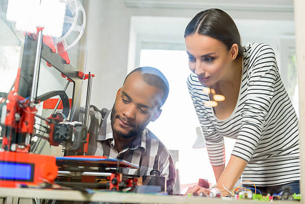 Smart man and woman watching 3d printing - foto stock