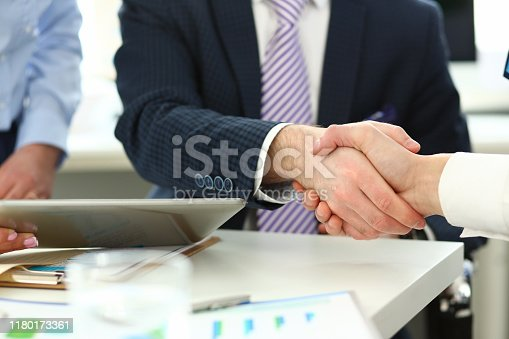 Focus on witty boss in white shirt and striped tie shaking hands with young manager. Business male perform friendly gesture towards colleague biz partner. Company meeting concept. Blurred background