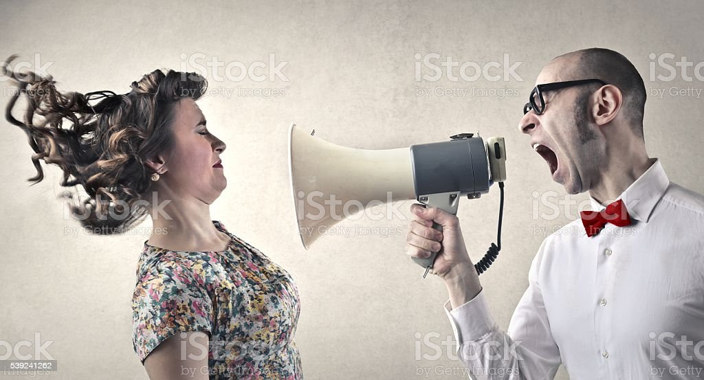 Smart man screaming at woman through megaphone foto de stock libre de derechos