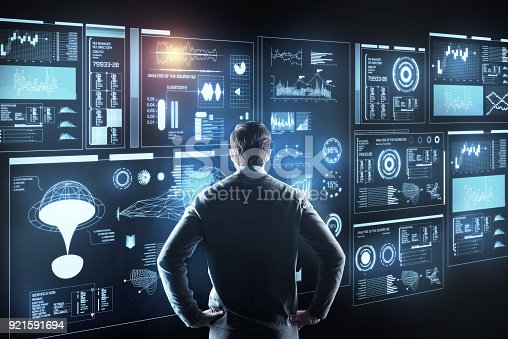 istock Smart man thinking while looking at the giant screen 921591694