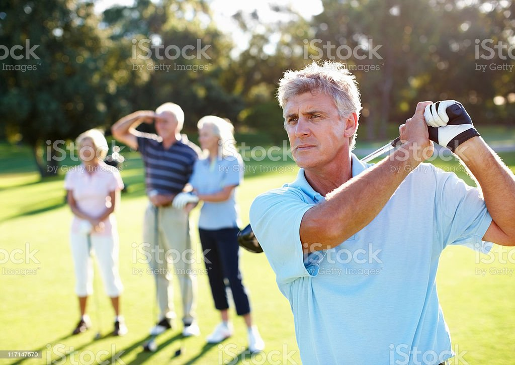 Smart, mature golfer swinging stock photo