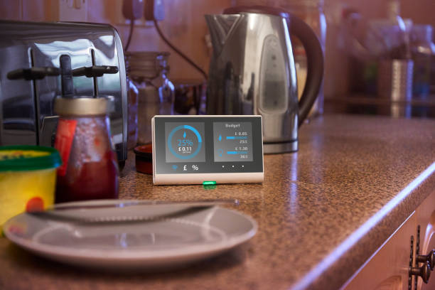 Smart meter in kitchen of home Smart meter showing the current energy output of the home smart thermostat stock pictures, royalty-free photos & images