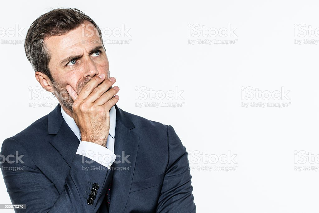 smart middle aged businessman thinking, looking up, hiding his mouth stock photo
