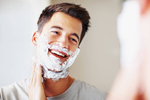 smart middle aged man applying shaving cream - shaving cream stock pictures, royalty-free photos & images