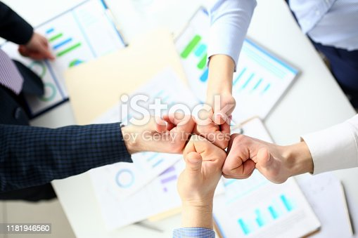 Close-up of friendly business collective performing cooperation gesture to greet presumptive boss or colleagues and show increased level of cohesion and solidarity. Company meeting concept