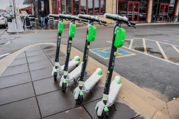 Smart personal mobility_ Four Lime electric scooters parked on the sidewalk on Cherry Street in the snow with shops and cars parked along the street and an outside cafe behind - selective focus. stock photo