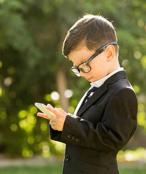 smart phone und kind, gekleidet als geschäftsmann - kleinkind busy bags stock-fotos und bilder