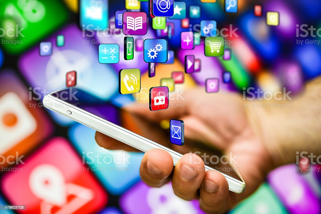 smart phone and multicolored apps A Human hand holding smart phone connected to the cloud and downloading multicolored software applications 2015 Stock Photo