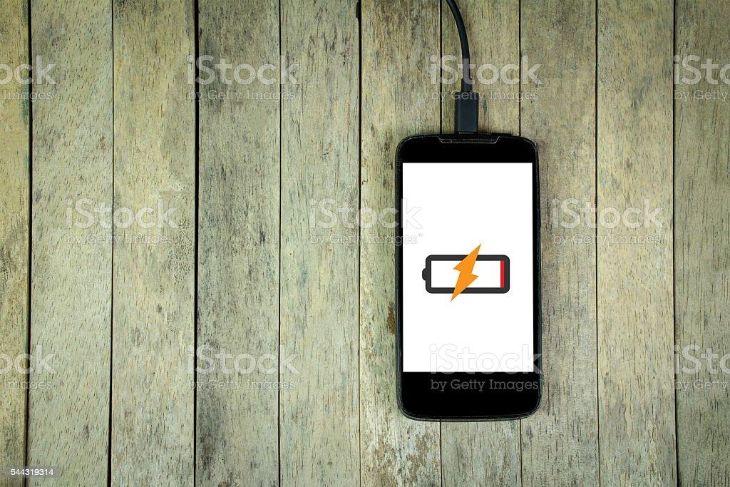 Smartphone lädt auf Holzhintergrund, Kopierplatz - Lizenzfrei Aufladen Stock-Foto