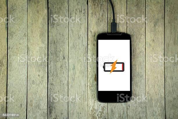 Smartphone Lädt Auf Holzhintergrund Kopierplatz Stockfoto und mehr Bilder von Aufladen