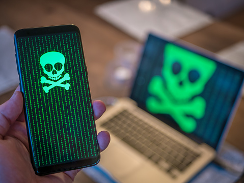 Smart Phone Is Hacked With Virus Computer In Background Stock Photo - Download Image Now