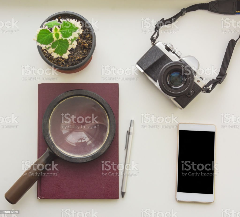 Smart phone magnifying glass on the burgundy notepad and photo camera royalty-free stock photo