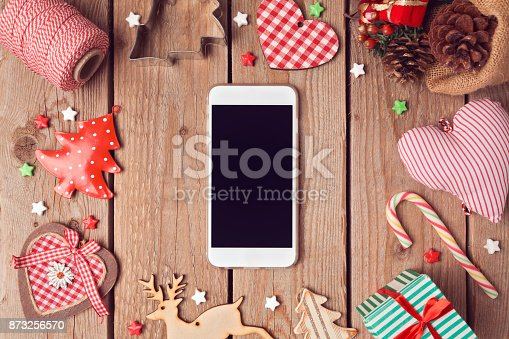istock Smart phone mock up with rustic Christmas decorations for app presentation. View from above 873256570