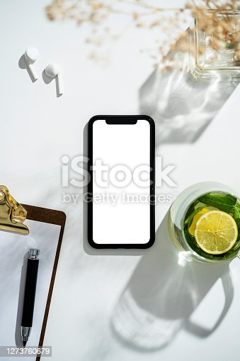 Sage tea in glass cup and blank screen mobile phone with clipping path on white background with long shadows