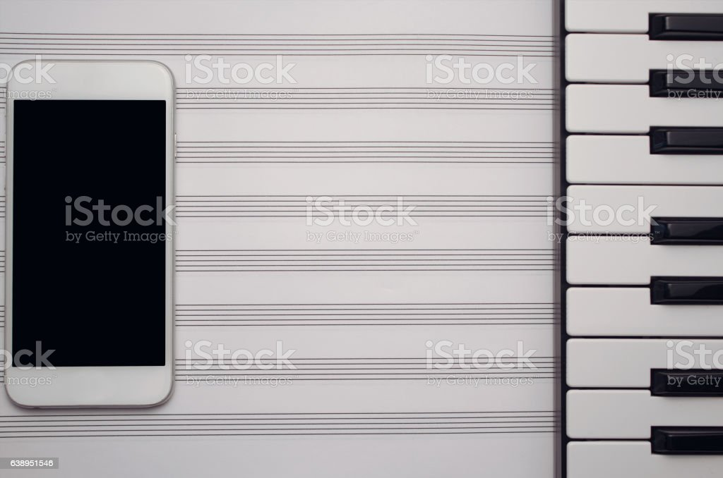 Smart phone, music sheet and music keyboard on wooden table stock photo