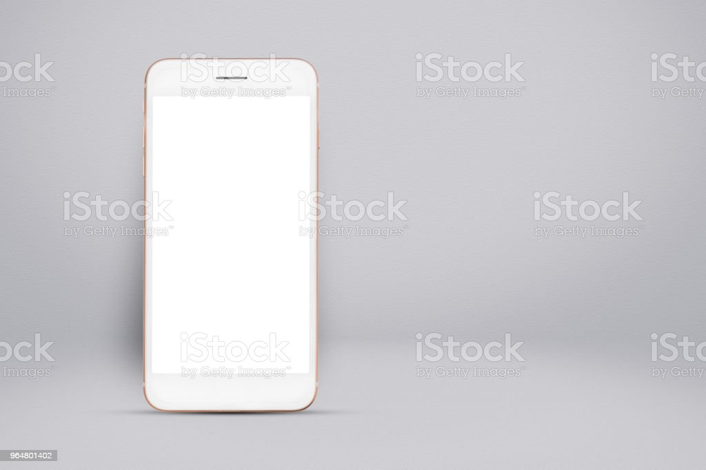Smart phone on gray gradient wall background. royalty-free stock photo