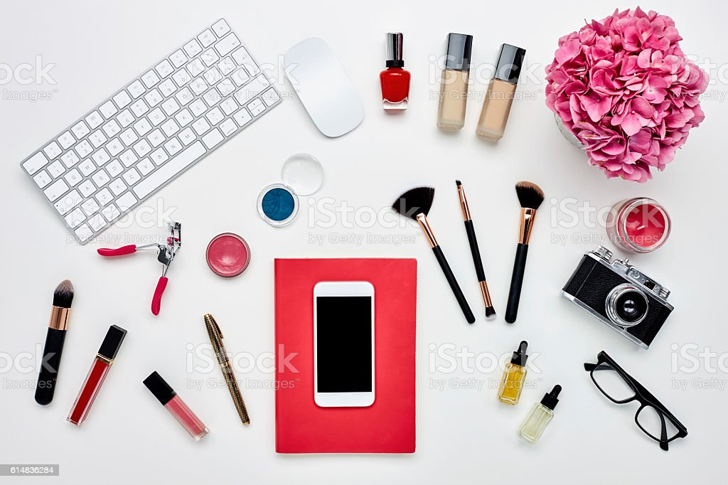 Smart phone on notepad surrounded with blogger's accessories