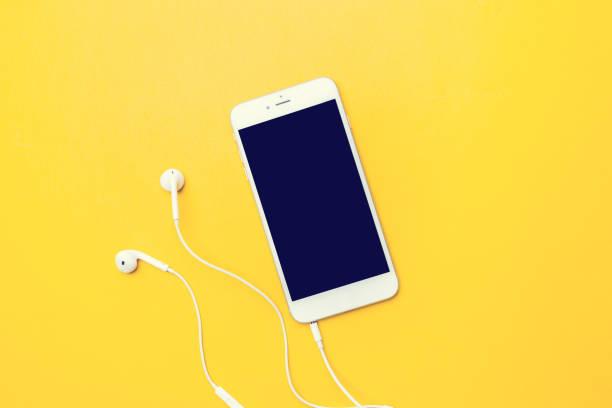 smart phone on yellow - słuchawka nauszna zdjęcia i obrazy z banku zdjęć