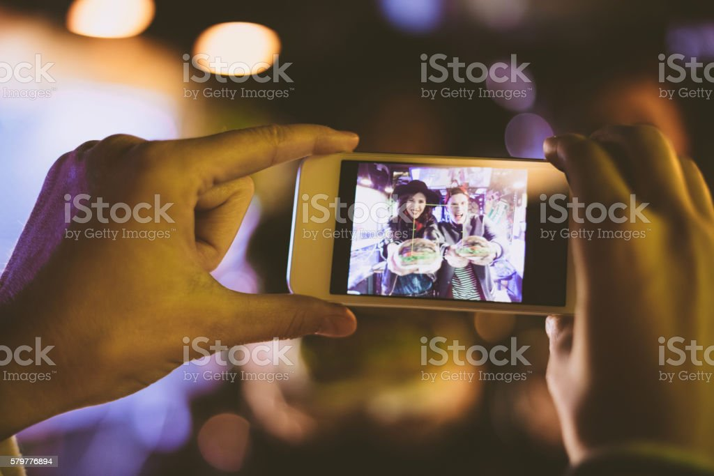 Smart phone screen with two girls eating burgers royalty-free stock photo