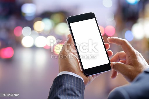 istock Smart phone showing blank screen in business man hand at walk street night 801267702