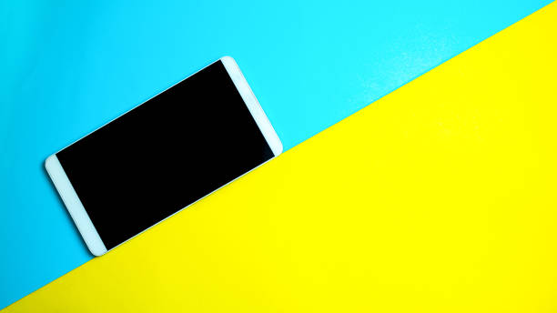 smart phone standing side way on yellow and blue color background stock photo