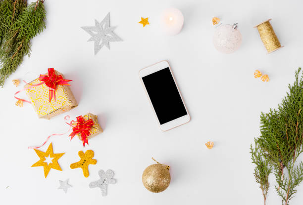 smart phone stylish mock up for branding for christmas time, christmas tree and decorations on white background, flat lay top view. stock photo