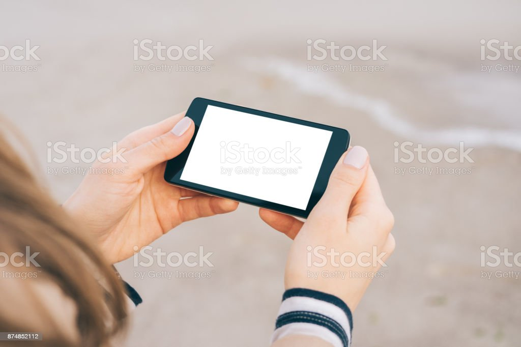 Smart phone with a white screen in female hands stock photo