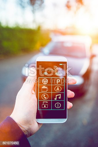501071464 istock photo Smart phone with app controls car from distance 501070450