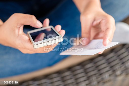 Woman use the mobile phone to calculate the bill on the other hand