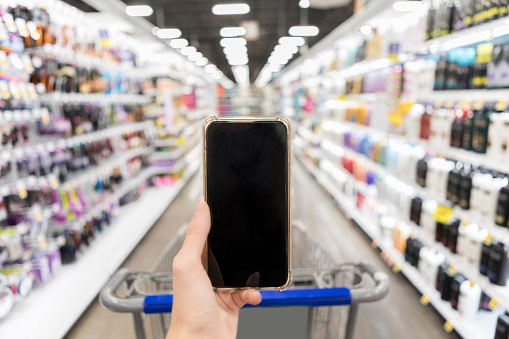 istock Smart phone with blank screen held up in supermarket 1041147464