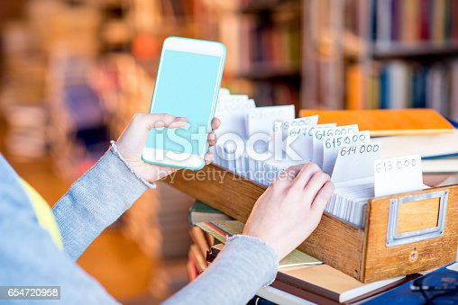 668340340istockphoto Smart phone with card catalogue 654720958