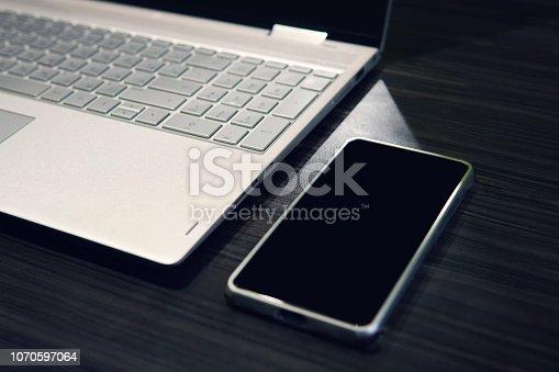 Smart phone with copy space screen and laptop on wooden table background. Empty black screen of a mobile left on the table near the computer. Use of digital gadgets at work. Phone display mockup
