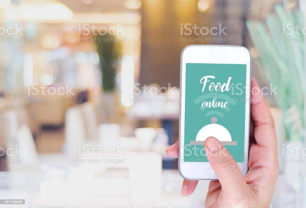 Slimme telefoon met voedsel online apparaat op scherm over blur restaurant achtergrond, voedsel online, voedsel levering concept foto