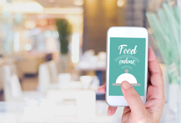 Smart phone with food online device on screen over blur restaurant background, food online, food delivery concept stock photo