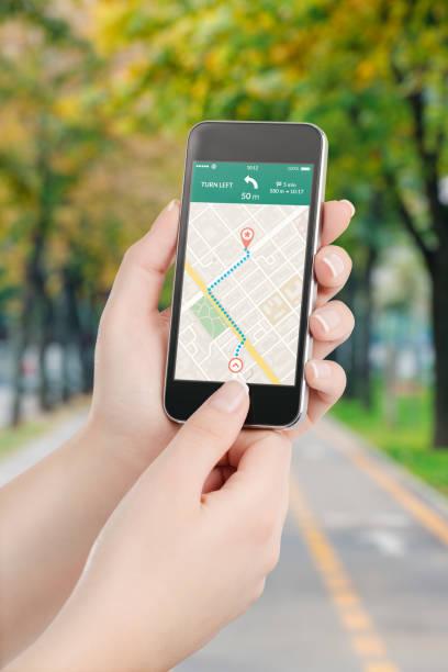 smartphone mit karte gps-navigation-applikation auf dem bildschirm - kompass wanderkarte stock-fotos und bilder