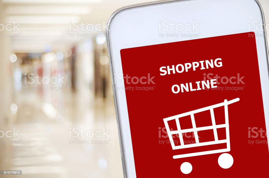 Smart phone with shopping on line on screen over blur store background, omnichannel, business and technology concept stock photo