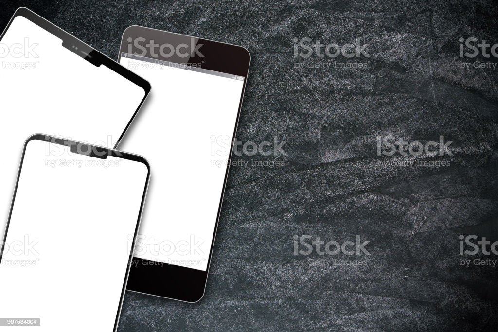 Smart phones on the blackboard background stock photo
