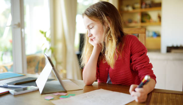 Smart preteen schoolgirl doing her homework with digital tablet at home. Child using gadgets to study. stock photo